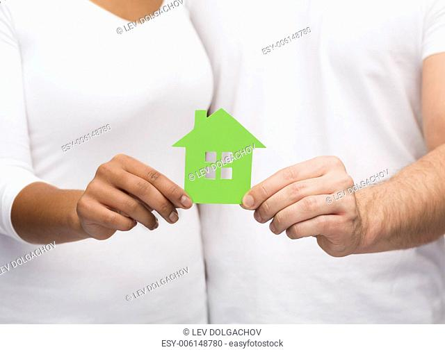 real estate, family and eco concept - closeup picture of couple hands holding green house