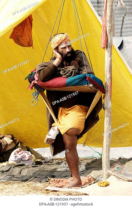 A sadhu from the Juna Akadha sits with his Trishul at their camp during the Ardh Kumbh Mela , , , India