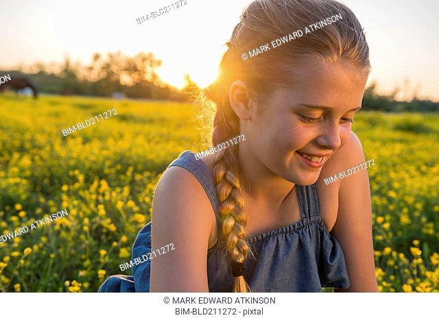 Caucasian girl smiling in field of flowers
