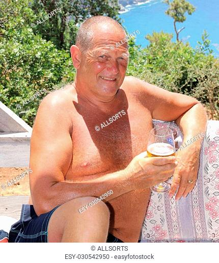 An englishman relaxing in the sunshine with a drink while on vacation, 2016