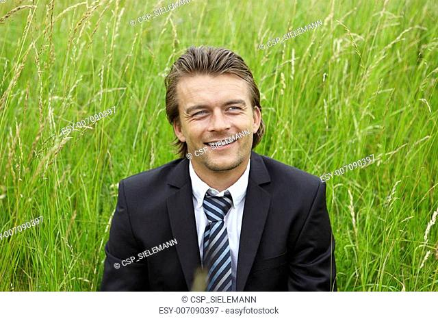 young businessman is sitting in a field