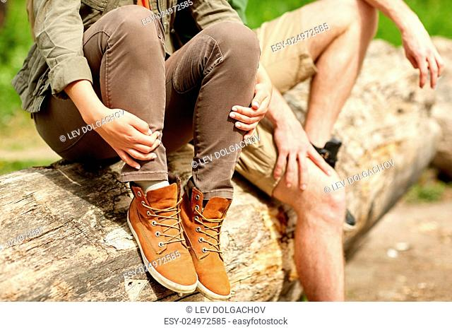 travel, hiking, tourism, footwear and people concept - close up of couple sitting on tree trunk outdoors