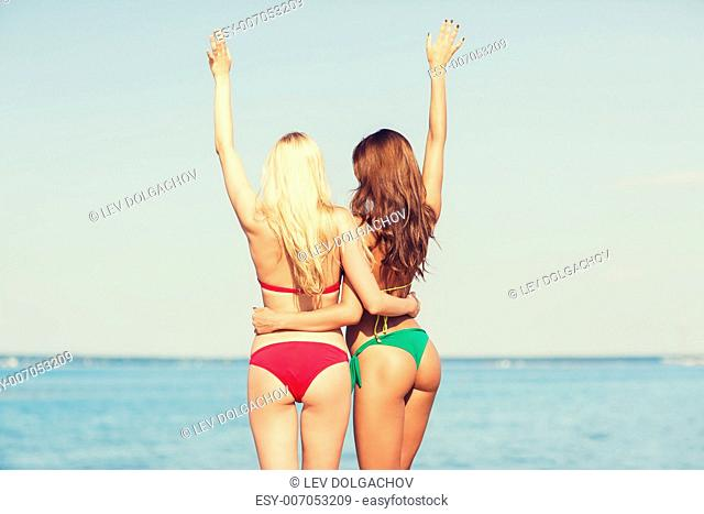 summer vacation, holidays, travel, gesture and people concept - two young women waving hands on beach from back