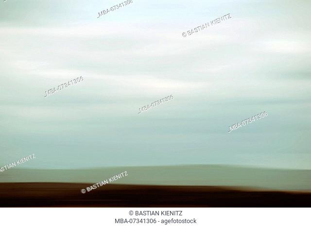The blurred outlines and silhouettes of a mountain range