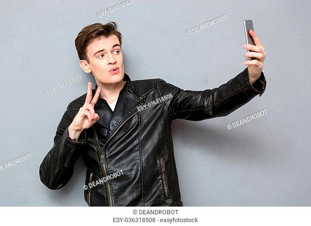 Portrait of a young man in leather jacket making selfie photo on smartphone over gray background