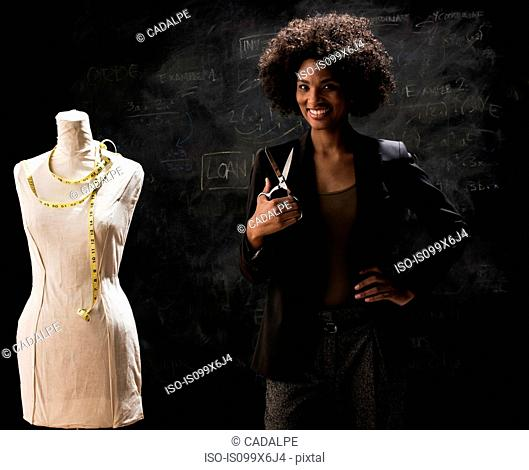 Businesswoman with tailors dummy and scissors