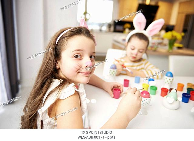 Portrait of smiling girl with sister sitting at table painting Easter eggs