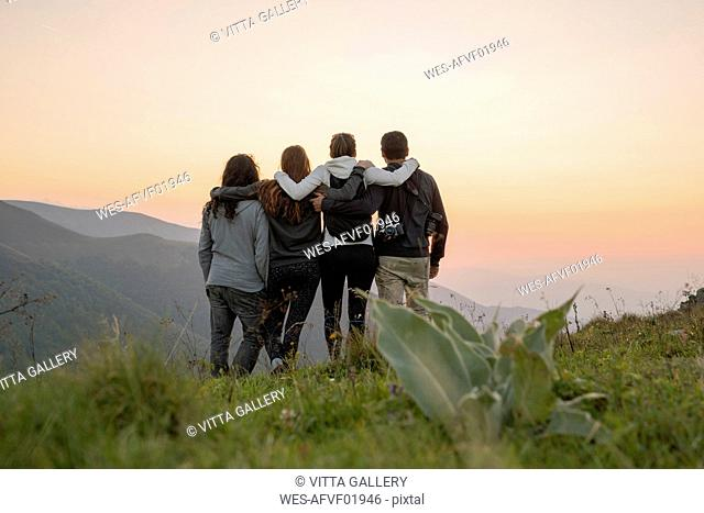Bulgaria, Balkan Mountains, group of hikers standing on viewpoint at sunset