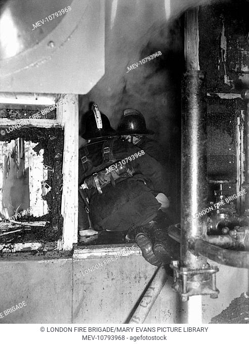 A major fire at Smithfield Poultry Market, London, on 23 January 1958 -- firefighters working at the head of a tunnel to gain entry into the basement