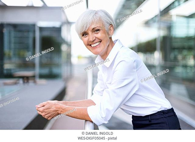 Portrait of happy senior woman leaning on railing in the city