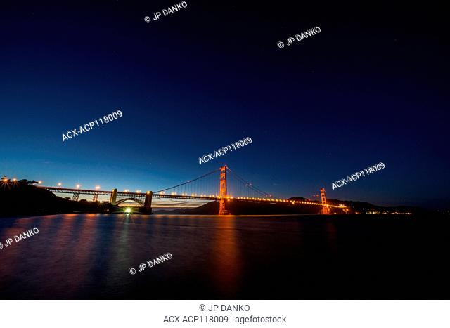 Golden Gate Bridge illuminated by streetlights rises above the water after sunset
