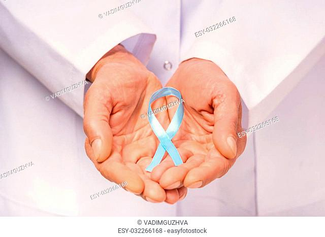 The social problem of male diseases. Close up of doctor hand with a blue ribbon. Isolated on white background