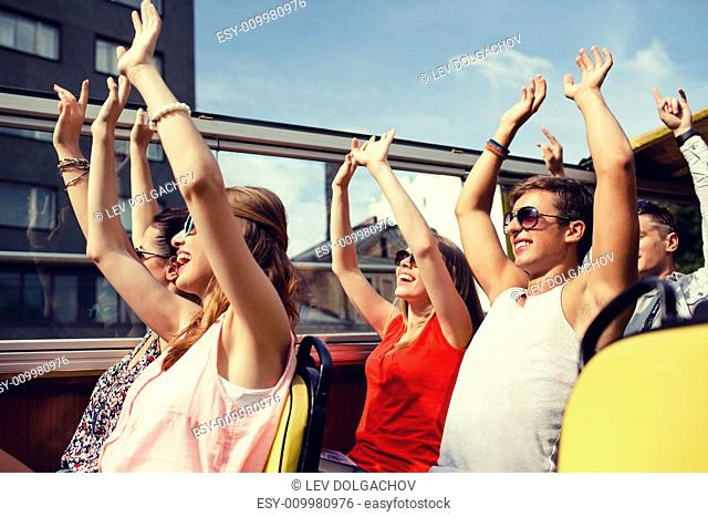friendship, travel, vacation, summer and people concept - group of smiling friends traveling by tour bus and waving hands