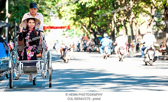 Vietnamese woman in Ao Dai dress on rickshaw, Hue, Thua Thien-Hue Province, Vietnam