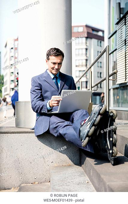 Businessman with inlineskates sitting down using laptop in the city