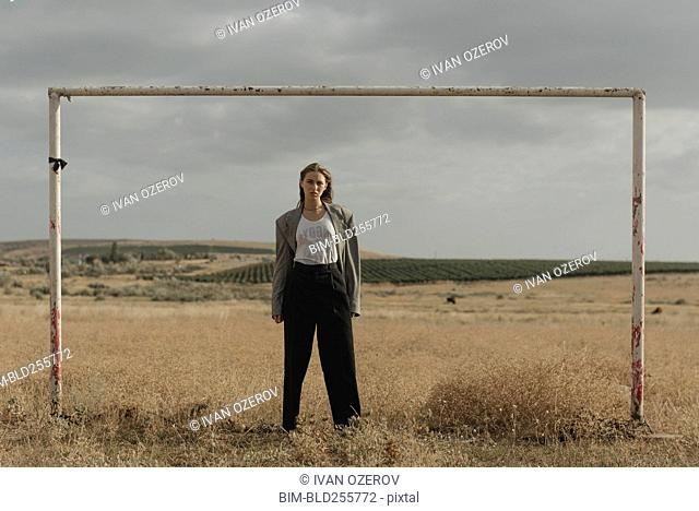 Serious location woman standing in worn soccer goal