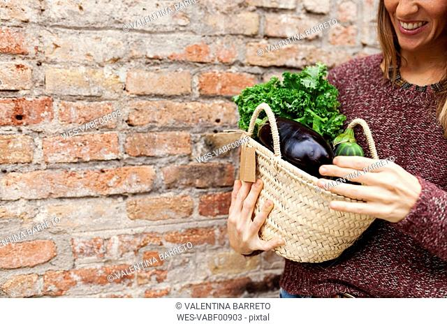 Smiling woman holding basket with fresh vegetables