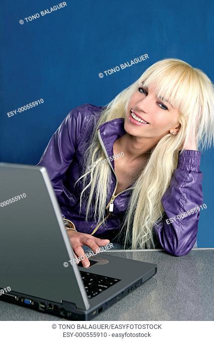 blonde fashion student laptop blue background
