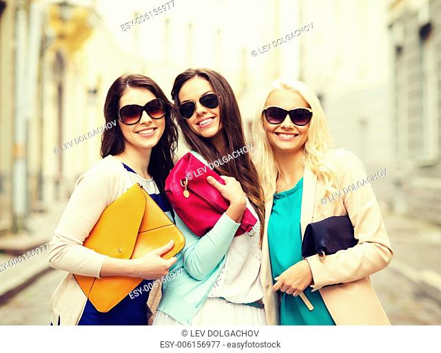 holidays and lifestyle concept - beautiful girls with bags in the ctiy