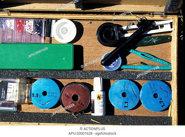 Angling equipment in an open tackle box