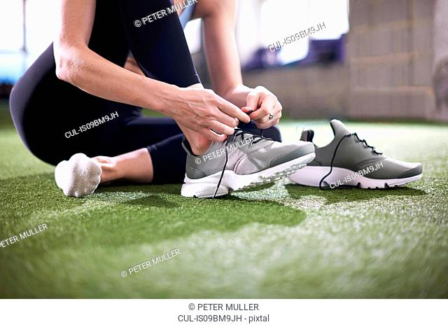 Woman tying shoelace in gym