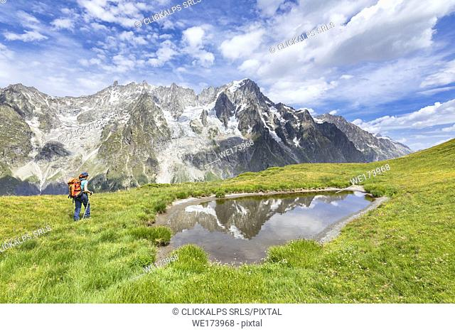 A trekker is walking on the Mont de la Saxe in front of Grandes Jorasses during during the Mont Blanc hiking tours (Ferret Valley, Courmayeur, Aosta province