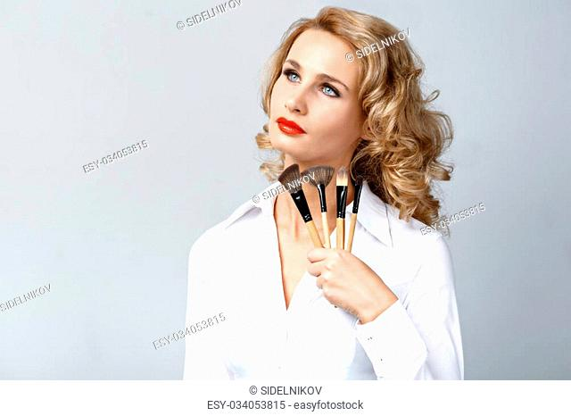 Portrait of beautiful caucasian blonde woman with curly hair standing on grey background. Young woman with red lips holding makeup brushes