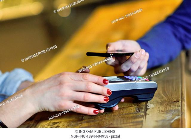 NFC Near Field Communication Mobile Payment. Hand holding smartphone paying on EDC machine
