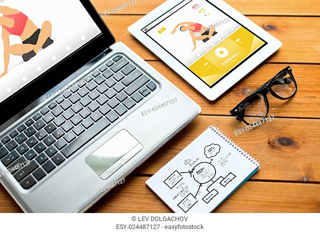 sport, responsive design and technology concept - close up of on laptop computer, tablet pc, notebook and eyeglasses with fitness application and scheme on...