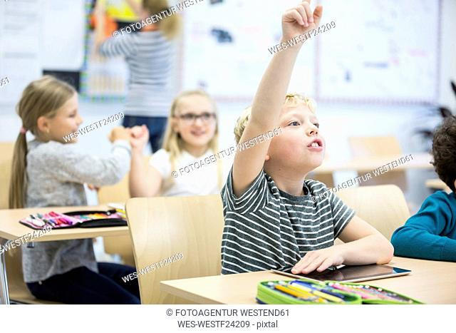 Schoolboy with tablet raising his hand in class