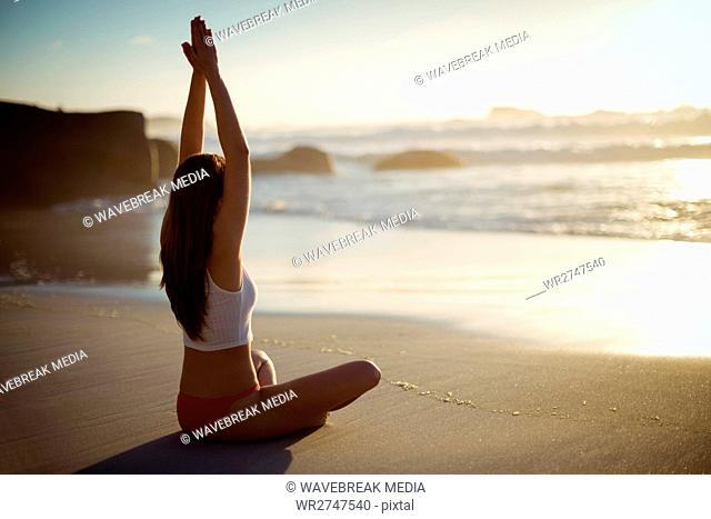 Beautiful woman performing yoga on beach