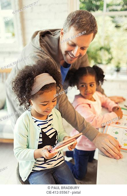 Multi-ethnic father and daughters with digital tablet