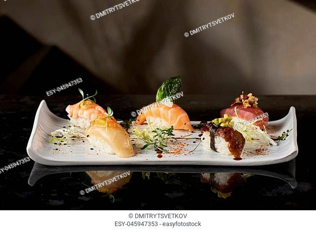 Sushi nigiri set on black marble background. Salmon, eel, prawn and tuna fish served on white plate with chopsticks