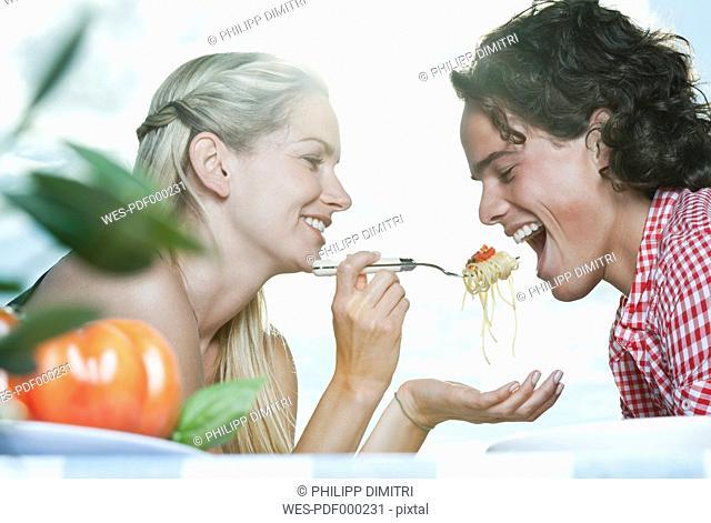 Italy, Tuscany, Young woman feeding spaghetti to man