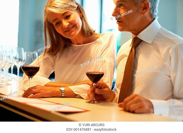 Portrait of happy senior couple in bar standing at counter