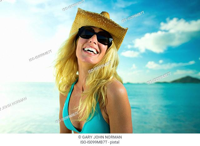 Happy woman in sunglasses and cowboy hat by the ocean