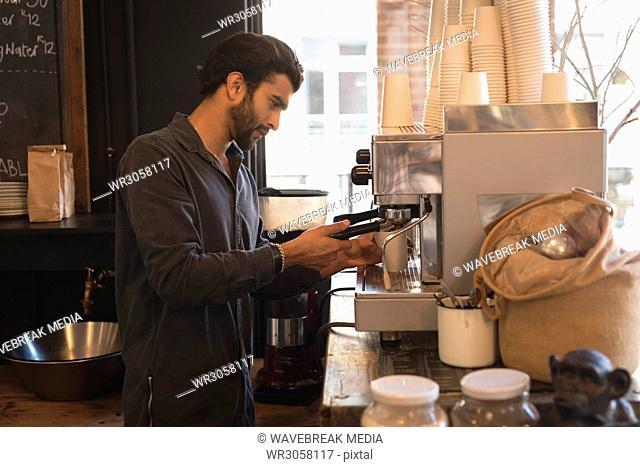 Barista using portafilter while preparing coffee
