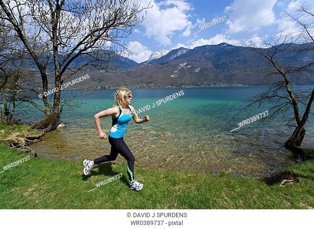 Woman jogging beside a mountain lake