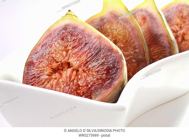 Fruit , Figs Ficus Carica Anjir two cut in four halve kept in s shape white plate on white background