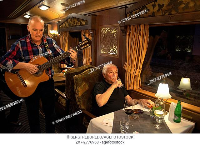 Inside of Transcantabrico Gran Lujo luxury train travellong across northern Spain, Europe. Interior of restaurant car. Guitar live music