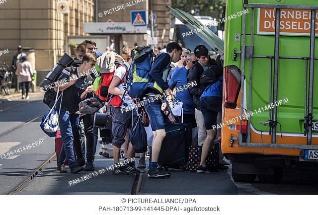 13 July 2018, Germany, Frankfurt: Passengers loading their luggage into a compartment of the bus in the middle of the street