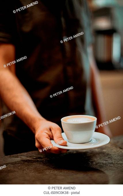 Barista placing cup of latte on cafe counter, cropped shallow focus