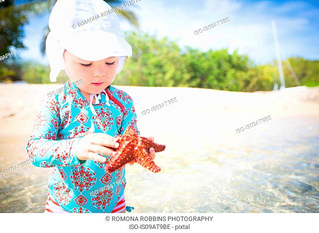 Girl on beach wearing swimear and sunhat holding starfish looking down, St. Croix, US Virgin Islands