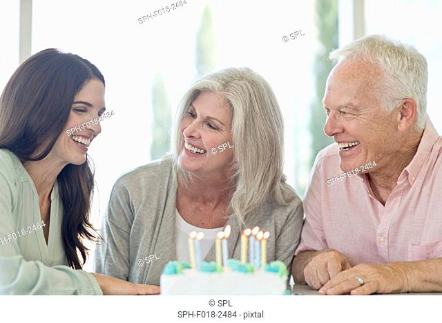 Senior couple and adult daughter with birthday cake
