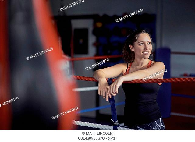 Young female boxer leaning on boxing ring ropes
