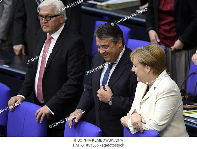 German chancellor Angela Merkel (CDU) talks to minister of the economy, Sigmar Gabriel (SPD, m), at the Bundestag in Berlin, Germany, 7 July 2016