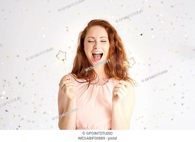 Portrait of shouting young woman with two sparklers