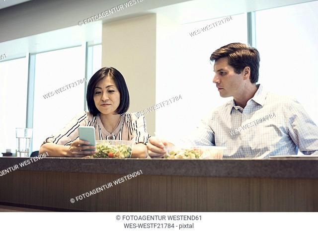 Colleagues in office having lunch together, woman looking at smart phone