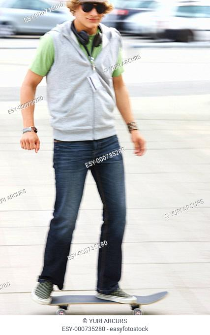 Full length of a handsome young man skateboarding on street