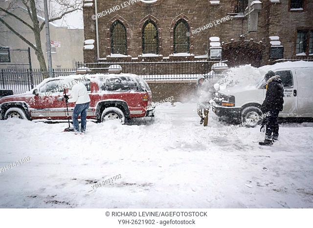 People shovel out their cars in Chelsea in New York during Winter Storm Jonas